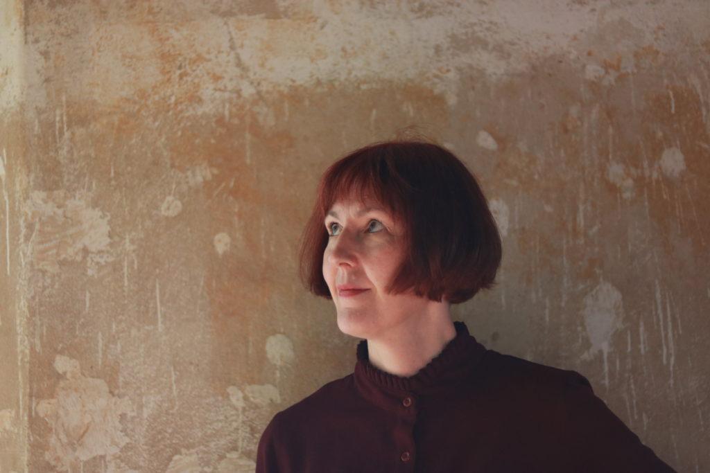 Annette vor rauher Wand
